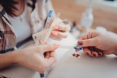 Vrouwelijke cliënt tijdens Gelmanicure met Manicure Displaying Samples van Patronen op spijkers royalty-vrije stock afbeelding