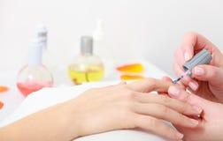 Vrouwelijke cliënt van schoonheidsspecialist de schilderende spijkers. Manicure in beauty spa salon. Stock Afbeeldingen