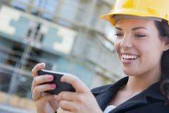 Vrouwelijke Contractant die Bouwvakker op Plaats Texting met Telefoon dragen Stock Afbeelding