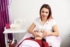 Vrouwelijke cosmetologist die aan de camera glimlachen terwijl het masseren van een vrouwelijke cliënt met een masker op haar gez royalty-vrije stock fotografie