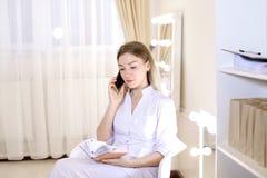 Vrouwelijke cosmetologist die door smartphone bij kabinet spreken Royalty-vrije Stock Fotografie