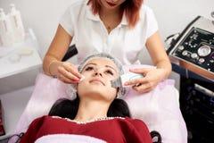 Vrouwelijke cosmetologist die een ultrasone klank gezichtsschil doen aan een vrouwelijke patiënt in een schoonheidssalon Royalty-vrije Stock Foto's