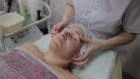 Vrouwelijke cosmetologist die gezichtsmassage doen aan bejaarde in cosmetological kliniek stock videobeelden