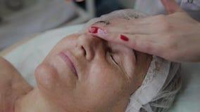 Vrouwelijke cosmetologist die gezichtsmassage doen aan bejaarde in cosmetological kliniek stock video