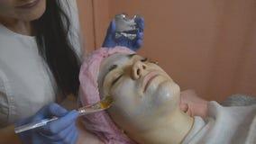 Vrouwelijke cosmetologist die tot kosmetisch gezichtsmasker maken aan de vrouwelijke cli?nt op het de kosmetiekcentrum stock video