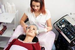 Vrouwelijke cosmetologist geeft het gezichts schoonmaken met een roterende borstel aan een mooie donkerbruine vrouw in een schoon royalty-vrije stock fotografie