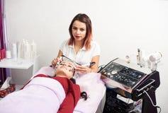 Vrouwelijke cosmetologist kijkt aan de camera terwijl het doen van gezichtsmassage aan een patiënt in een witte schoonheidsstudio royalty-vrije stock afbeeldingen