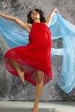Vrouwelijke danser met wervelende blauwe stof en grijze achtergrond Royalty-vrije Stock Afbeeldingen