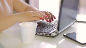 Vrouwelijke de druktekst van het handenclose-up op laptop en drank van een beschikbaar glas stock footage