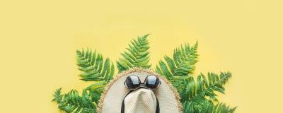Vrouwelijke de hoed van het strandstro en varenbladeren op geel Hoogste mening Het concept van de de zomerreis banner stock afbeelding