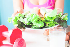 Vrouwelijke de saladeschotel van de geschiktheidsholding en domoren op lijst, Gezond levensstijlconcept Stock Afbeeldingen
