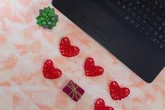 Vrouwelijke Desktop met laptop, harten en een kleine gift royalty-vrije stock afbeeldingen