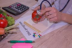 Vrouwelijke Diëtist Examining Fresh Vegetables met Stethoscoop Stock Foto's