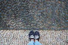 Vrouwelijke die benen in tennisschoenen en jeans, op de weg met stenen wordt bedekt stock foto