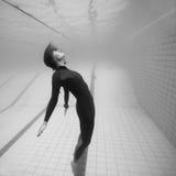 Vrouwelijke die duiker in ruimte onderwater wordt opgeschort Royalty-vrije Stock Foto's