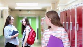 Vrouwelijke die middelbare schoolstudent over door studenten in gang wordt gesproken stock footage