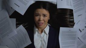 Vrouwelijke die onderneemster met administratie, verbergend gezicht in verschrikking wordt overweldigd, close-up stock videobeelden