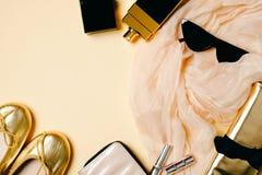Vrouwelijke die toebehoren op beige achtergrond worden geplaatst Sjaal, zonnebril, gouden de zomerpantoffels, kosmetische zak, pa stock afbeelding