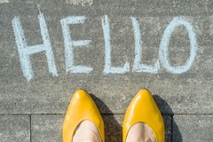 Vrouwelijke die voeten met tekst hello op asfalt wordt geschreven stock afbeelding