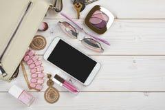 Vrouwelijke dingen die van handtas op houten achtergrond met copyspace vallen Stock Foto's