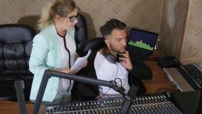 Vrouwelijke directeur met blad van document en de mens in oortelefoons bij radiostudio stock video