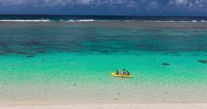 Vrouwelijke en kleine jongens die kano op een tropische lagune paddelen stock footage