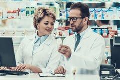 Vrouwelijke en Mannelijke Apotheker Working in Drogisterij stock foto