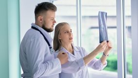 Vrouwelijke en mannelijke arts die in witte laag het x-ray richten op momentopname herzien stock videobeelden