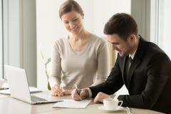 Vrouwelijke en mannelijke bedrijfsleiders die contract ondertekenen stock afbeelding