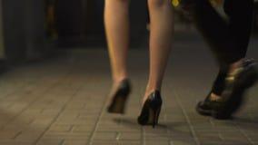 Vrouwelijke en mannelijke benen die onderaan straat voorbij showcase, die aan nachtclub, datum lopen gaan stock footage