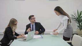 Vrouwelijke en mannelijke businesspartners werken in het bureau samen en de secretaresse brengt koffie stock videobeelden