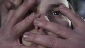 Vrouwelijke en mannelijke handen met gotische tatoegeringen en nagellak die dramatisch en het mannelijke gezicht raken uitrekken stock footage