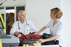 Vrouwelijke en mannelijke ziekenwagen arts die vóór opdracht spreken royalty-vrije stock foto