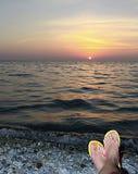 Vrouwelijke enkels tegen een overzees landschap bij zonsondergang Stock Foto