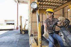 Vrouwelijke fabrieksarbeider die weg terwijl drijfvorkheftruck kijken Stock Afbeeldingen
