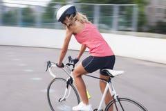 Vrouwelijke fietser die oefening op rasfiets maken. beeld met panning royalty-vrije stock fotografie