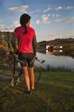 Vrouwelijke fietser door wijngaardmeer bij zonsondergang stock afbeeldingen