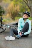 Vrouwelijke fietser in pijn die haar verwond been houden royalty-vrije stock foto's