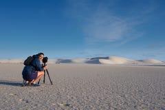 Vrouwelijke fotograaf die landschapsfoto van zandduinen nemen Stock Fotografie