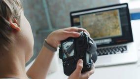 Vrouwelijke fotograaf het herzien foto's op haar camera thuis stock videobeelden