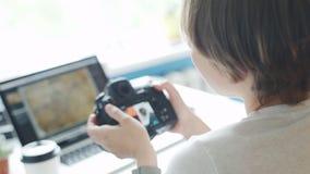 Vrouwelijke fotograaf het herzien foto's op haar camera thuis stock footage