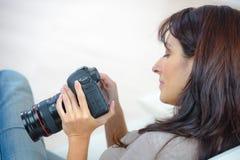 Vrouwelijke fotograafzitting op bureau met laptop Royalty-vrije Stock Foto's