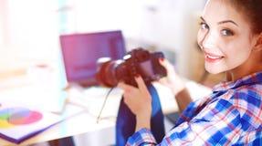 Vrouwelijke fotograafzitting op het bureau met laptop Stock Afbeelding