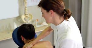 Vrouwelijke fysiotherapeut die achtermassage geven aan een patiënt stock videobeelden