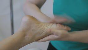 Vrouwelijke fysiotherapeut die voetmassage voor vrouw in de kliniek maken stock videobeelden