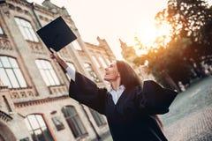Vrouwelijke gediplomeerde dichtbij universiteit stock afbeeldingen