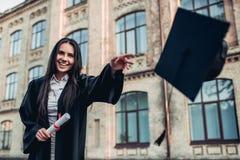 Vrouwelijke gediplomeerde dichtbij universiteit stock fotografie