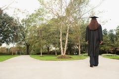 Vrouwelijke gediplomeerde die onderaan een weg lopen stock foto