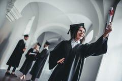Vrouwelijke gediplomeerde op universiteit stock foto's