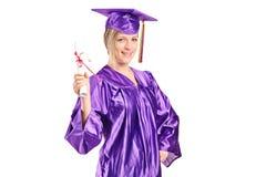 Vrouwelijke gediplomeerde student die een diploma houden stock afbeelding